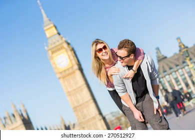 Happy young couple enjoying a piggyback ride in London with Big Ben amd Westminster palace on background. They are both wearing sunglasses and spring clothing.