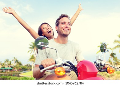 Happy young couple enjoying scooter ride against sky. Cheerful woman with arm raised screaming while man driving vehicle. Carefree tourists enjoying their summer vacation.