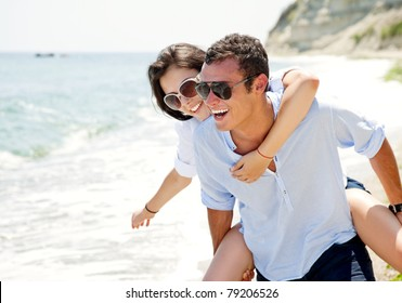 Happy young couple enjoying a solitary beach backriding