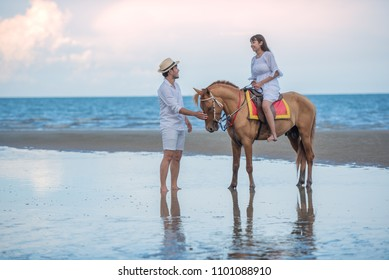Happy young couple with enjoying together, woman riding a hose and her boyfriend to lead a horse on the summer beach, romantic couple spending time concept.