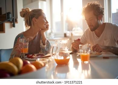 Ein glückliches, junges Paar, das sich an einem schönen sonnigen Morgen bei einem gemeinsamen Frühstück wunderschöne Momente gönnt. Beziehung, Liebe, zusammen, Frühstück