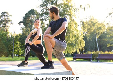 Happy young couple exercising together in a park.