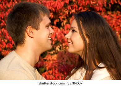 Happy young couple face to face in the autumn park with red leaves