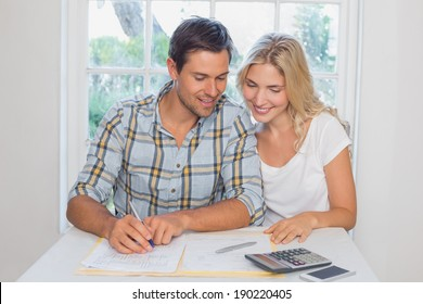 Happy young couple with financial documents and calculator sitting at home