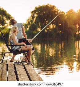 Happy young couple fishing on the lake