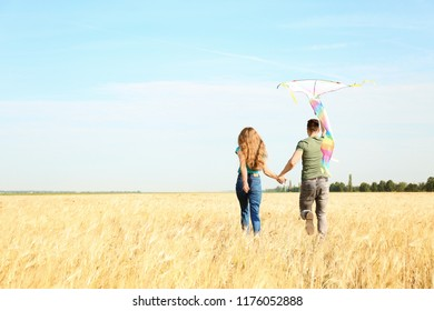 Happy young couple flying kite in a field