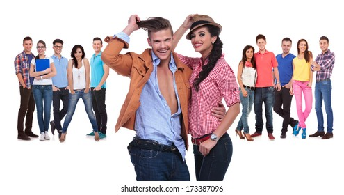 happy young couple in front of a large team of casual people on white background