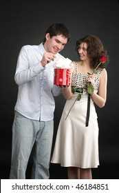 Happy young couple with gift and red rose isolated on a white background.