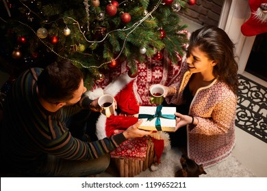 Happy young couple giving present and drinking tea at home at Chrismas time. Christmas tree and gift boxes.