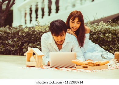 Happy young couple go picnic and dating at the park in summer.