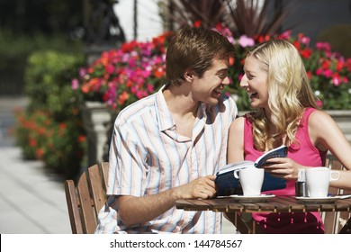 Happy young couple with a guidebook sitting at the outdoor cafe