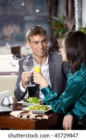 Happy young couple has dinner at restaurant
