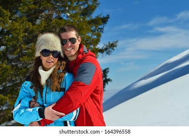 Happy young couple has fun on fresh snow at beautiful winter sunny day on relaxing vacation