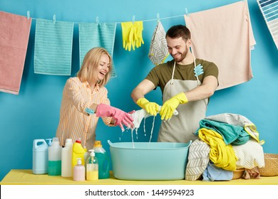 happy young couple has washed dirty clothes and squeezes out the water with hands. close up photo. isolated blue background. studio shot. lifestyle