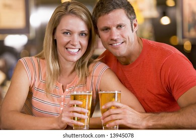 Happy young couple having beers at a bar