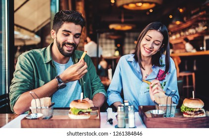 Happy young couple having breakfast in a cafe. Love, dating, food, lifestyle concept