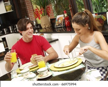 Happy young couple having a breakfast in a kitchen.
