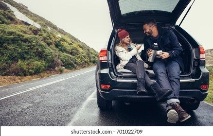 Happy young couple having a coffee break during road trip in countryside. Man and woman sitting in car trunk and having coffee.