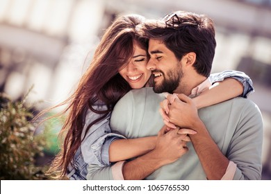 Happy young couple having fun outdoors and smiling.