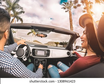 Happy young couple having fun during road trip in convertible car - Romantic lovers enjoying time together driving cabriolet auto in luxury vacation in a tropical city - Love and youth lifestyle