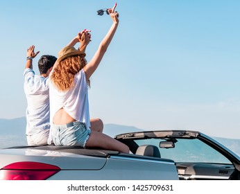 Happy young couple having fun in convertible car on beautiful summer day. Selective focus. Motion Blur.