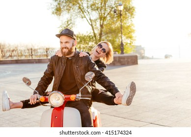 happy young couple having fun riding the scooter during sunset or sunrise. Couple on motorbike in city