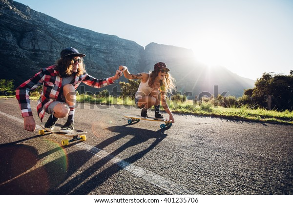 Happy young couple having fun with skateboard on the road. Young man and woman skating together on a sunny day.