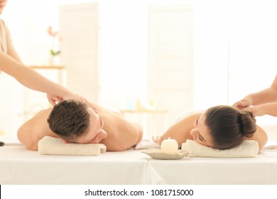 Happy young couple having massage in spa salon