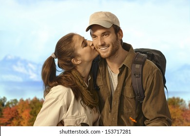 Happy young couple hiking together in nice autumn weather, woman kissing man.