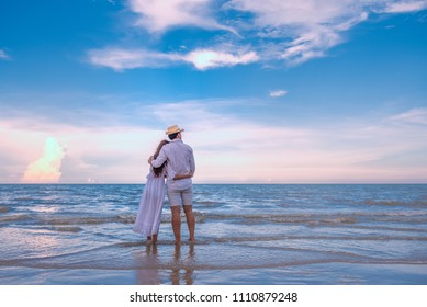 Happy young couple holding each other and laughing with enjoying together on the summer beach, we can see the blue sea stretching to the horizon,  romantic couple spending time concept.