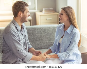 Happy young couple is holding hands, looking at each other and smiling while sitting on the couch at home
