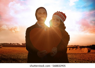 Happy young couple holding heart shape paper against countryside scene