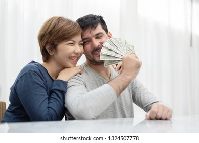 Happy Young couple holding money for buy their new house. US Dollar bills. Saving.