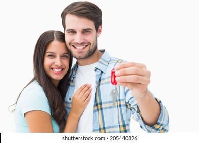 Happy young couple holding new house key on white background