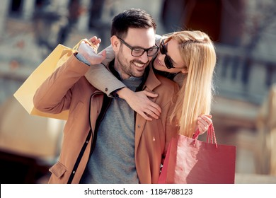 Happy young couple holding shopping bags on their shoulders while walking  after shopping.