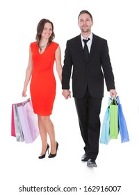 Happy Young Couple Holding Shopping Bags On White Background