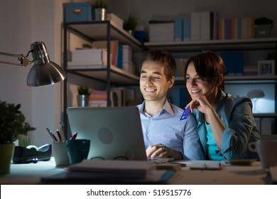 Happy young couple at home surfing the web, networking and online shopping late at night, she is holding a credit card
