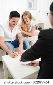 happy young couple at home in transaction signing contract with a business woman