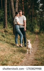 Happy young couple hugging in the forest with a small corgi dog. Summer nature, woman and man dressed in white t - shirts and jeans,.