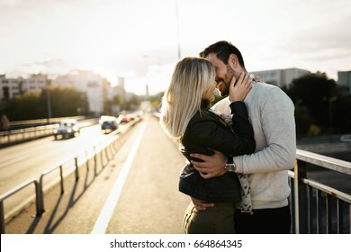 Happy young couple hugging and kissing on bridge