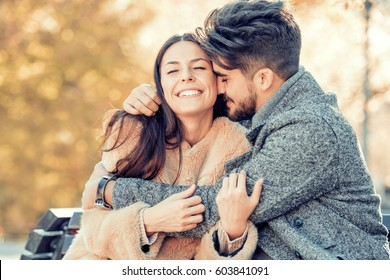 Happy young couple hugging and laughing outdoors.