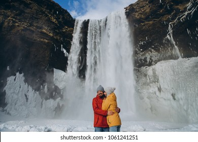 happy young couple hugging near beautiful skogafoss waterfall in iceland