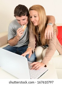 Happy Young Couple internet shopping with credit card at home