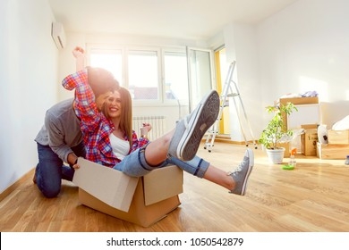 Happy young couple just moved into new home unpacking boxes; having fun