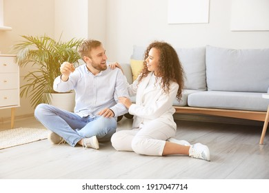 Happy young couple with key in their new flat