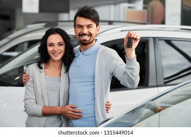 Happy young couple with keys from a new car after automobile purchase in dealer showroom.