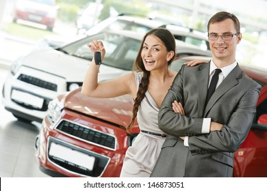 Happy young couple with keys from new car after automobile purchase in dealer showroom