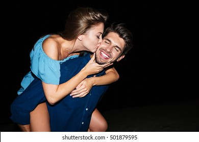 Happy young couple kissing and having fun on the beach at night