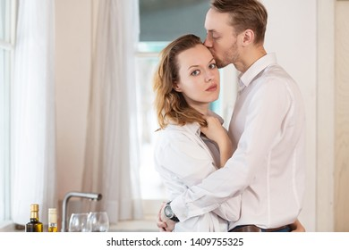 Happy young couple kissing and hugging while cooking breakfast in the kitchen of their country house rejoicing housewarming