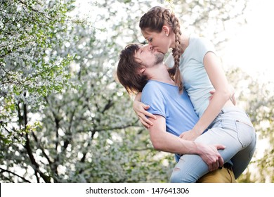 happy young couple kissing outdoor in the park